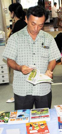 市立図書館で開かれている教科書展示会で、各社の教科書に見入る玉津教育長(4日午後)