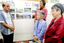 慶田盛教育長(左)を激励する仲村代表(右から2番目)ら=23日午前、竹富町教委