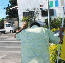 通行する車に頭を下げ、支持を訴える運動員(写真は一部加工しています)=1日午前、石垣市内