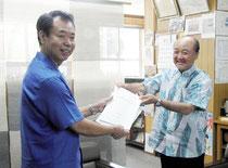 策定した観光計画を答申する上勢頭委員長(右)=町役場