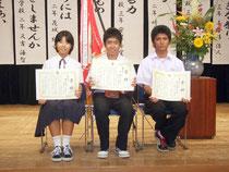(左から)優秀賞の小室なつみさん、最優秀賞の崎原永都君、優秀賞の仲山忠扶君=11日午後、市民会館中ホール