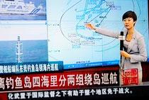 10日、「海警指令センター」から生中継しているとされる中国国営放送のキャスター。尖閣周辺の海図を使い「海警」と日本の巡視船の位置を説明している(中国国営放送のテレビ画面より)