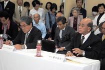 義家政務官の指導に反論する慶田盛教育長(右)と竹盛委員長。反対派の住民も詰めかけた=1日午後、町教委