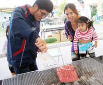 家族で石垣牛のバーベキューを楽しむ大会来場者=24日午後、市中央公園陸上競技場入口