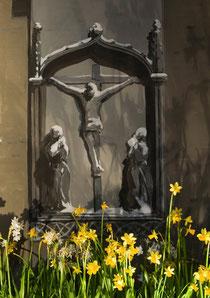 Osterglocken vor der Kreuzgruppe erinnern an Ostern, an die Auferstehung, Milieukrippe Lyskirchen