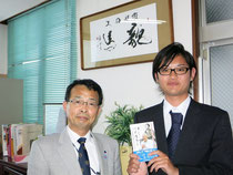 高知大学大学院の北村暢章君。竹内土佐郎先生からいただいた書「維新回転 龍馬」の前で。
