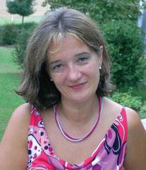Claudia Wessel mit buntem Sommerkleid und Halskette im Garten