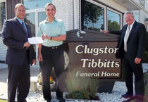 Mark Tibbitts (left) handing a donation from Clugston-Tibbitts Funeral Home to Dan Wise, president of the McDonough County Historical Society. Business partner Scott Conlin (right) looks on. Steve Tibbitts unavailable for the photo.