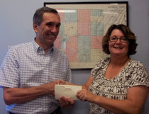 Eva Fisher (right), president of the McDonough County Genealogical Society, presents a donation to Dan Wise, president of the McDonough County Historical Society, supporting the cemetery sign project.