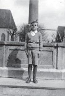 Rolf Weil aus Zehnjähriger vor dem Ochsenbrunnen in Nürtingen, die dunklen Augengläser trug er wegen eines Augenleidens, 1931/32, aus WERNER 1998, S. 126