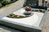 """Doppelgrab mit """"Spiralen-Symbol"""" und Blumen"""