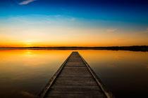 Le ponton pour embarquer sur le lac, devant un couché de soleil qui se reflette dans l'eau douce et calme