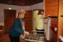 Hildegard und Anette holen das Geschirr aus den Schränken