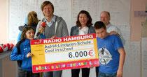Radio Hamburg Moderator Philipp Kolanghis übergibt den Scheck.