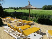 Sonnenstrand: Gelbe Liegen mit Sonnenschirm, Sandstrand, im Hintergrund ein Kornfeld