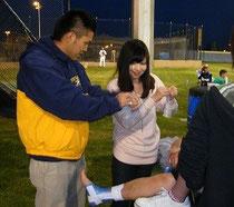 先輩トレーナーにテーピングを教わるミサキさん。