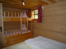 Die Almhütte bietet ein Doppelzimmer mit zusätzlichen Stockbett