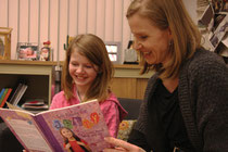 Desiree Sweetapple, 10, left, and her mom Tracey take a look at a book about living with ADHD. Desiree became more interested in learning about her condition after attending the GLOW for LD/ADHD program. TESSA CLAYTON/AIRDRIE ECHO