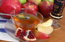 テーブルにはざくろ、りんご、蜂蜜などが