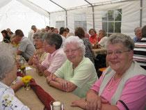 Foto vom Gemeindefest - Menschen an Tischen