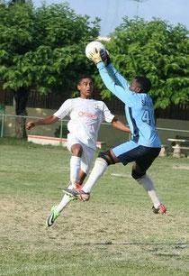 Leury López de Moca uniforme blanco disputa un balon frente a un jugador del ISA