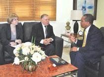 El rector de la UASD, maestro Mateo Aquino Febrillet, mientras conversa con el embajador de los Estados Unidos en el país, durante una visita que éste le giró en su despacho.  Observa en el extremo izquierdo, la agregada cultural de la embajada Katherine