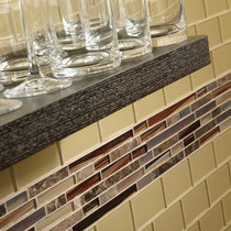 Gold, red, and brown glass and stone mosaics on a backsplash