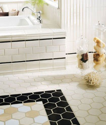 White, cream, and black bathroom tile with hexagons, subway tile, and beadboard.