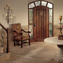 Brown and beige travertine stone floors and wainscoting in a traditional entryway