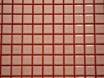 Red grout in between small pink tiles.