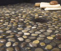 Multi-color pebbles on a shower floor with black grout