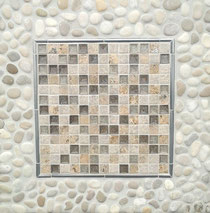 "A tile backsplash with a center of 1"" square marble and glass mosaic in cream and grey tones, framed by a pewter border, with an outside field of light off-white and grey round pebbles"