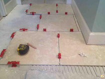 Red seam clips level a large format tile installation.