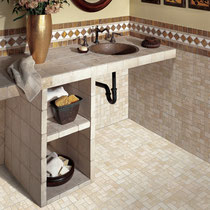A bathroom vanity with beige tiles that match the wainscoting and mosaic tile floor.