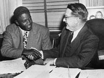 Jackie Robinson stringe la mano a Branch Rickey dopo la firma del suo primo storico contratto di major league baseball, 1945 @ Corbis