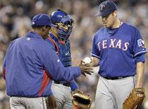 Il Manager dei Texas Ron Washington si fa consegnare la palla da Colby Lewis (foto da Yahoo! sports)