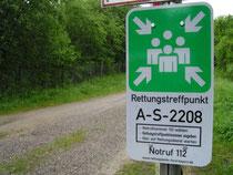 Das Foto zeigt neben einer Forststraße das offizielle Hinweisschild mit der Bezeichnung des Rettungstreffpunkts.