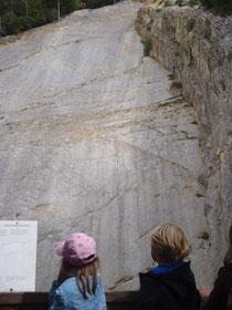 Kinder vor der Felswand mit den Saurierspuren