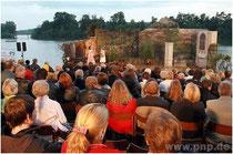 Zuschauer blicken in der Abenddämmerung auf die Seebühne