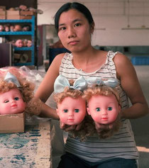 Chinoise présentant des poupées blondes aux visages de type européen
