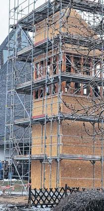 Noch vom Baugerüst umhüllt steht der Glockenturm bei der Glockenweihe. Durch das schlechte Wetter gab es Bauverzögerung.