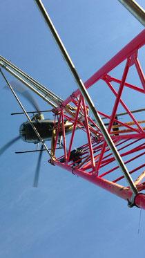 Industriekletterer von Proseil montieren einen Masten mit Helikopter