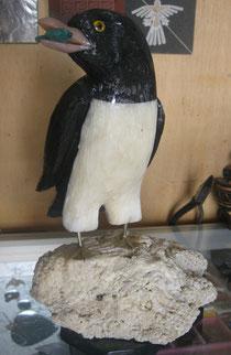 Pinguino echo en piedras peruanas, lleva un pez de piedra turqueza en el pico.