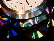 Bahnhofsuhr und farbige Reflexionen auf CDs