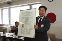 松尾前会長より小川会長へ認証状が引き継がれた