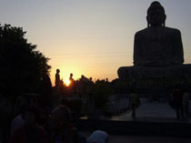 Statue of Buddha and Buddha disciples in Bodh Gaya, India, floating in the setting sun