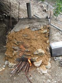 炭焼き窯の前面を赤土で覆う