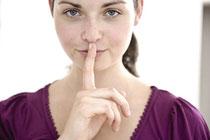Frau, die Zeigefinger auf den Mund legt