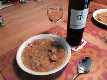 Kartoffeleintopf und eine Flasche sowie ein Glas Wein