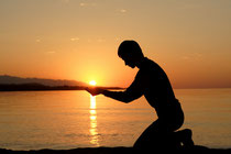 A man kneeling in worship at sunset on a beach